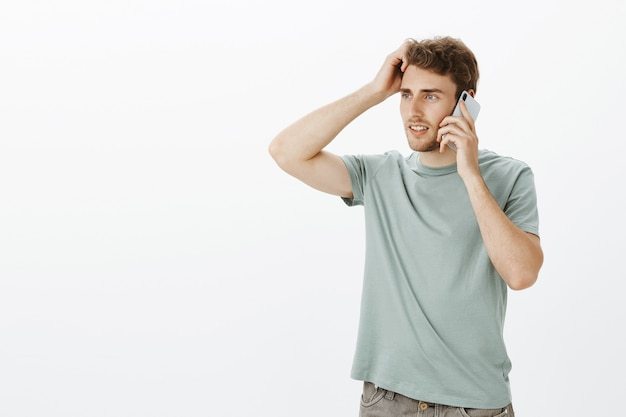 Fiducioso bel ragazzo biondo, guardando a sinistra e toccando i capelli tenendo lo smartphone vicino all'orecchio e parlando, discutendo di qualcosa e pensando a quale risposta