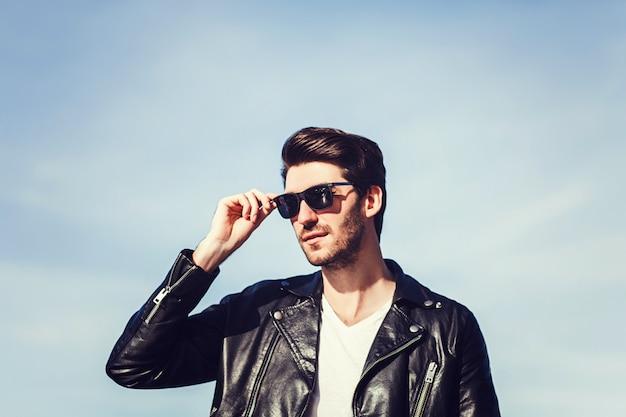 Fiducioso bell'uomo in occhiali da sole