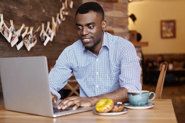 Fiducioso giovane impiegato afro-americano in abbigliamento formale che digita sul pc portatile