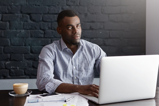Fiducioso giovane imprenditore africano seduto davanti al computer portatile aperto