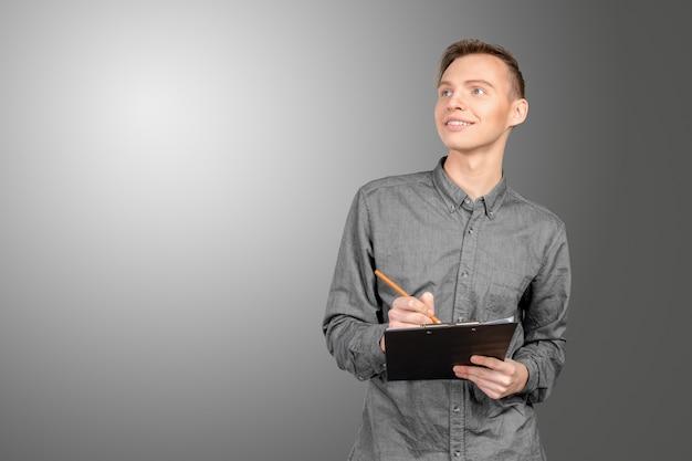 Fiducioso giovane uomo in camicia a prendere appunti nel suo pad