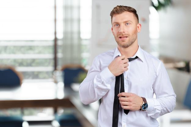 Fiducioso giovane uomo in camicia e cravatta regolando la cravatta