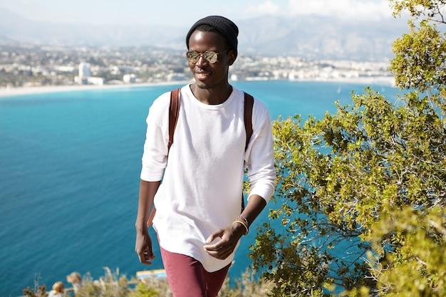 Fiducioso giovane viaggiatore maschio con zaino in piedi sulla montagna in riva al mare