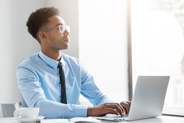 Fiducioso uomo d'affari che lavora al suo computer portatile