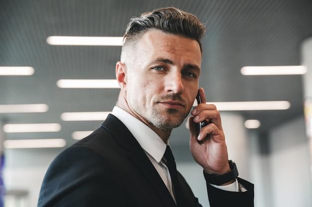 Fiducioso uomo d'affari maturo parlando al telefono cellulare
