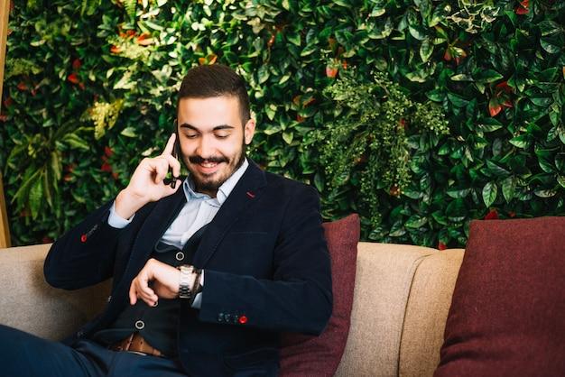 Fiducioso uomo d'affari tempo di controllo e telefono di conversazione