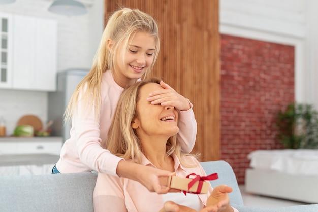Figlia adorabile che offre un regalo a sua madre