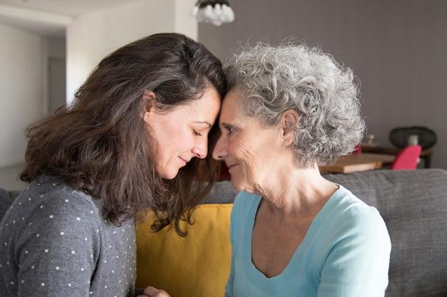 Figlia adulta e madre anziana toccando la fronte