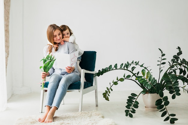 Figlia che abbraccia madre con biglietto di auguri