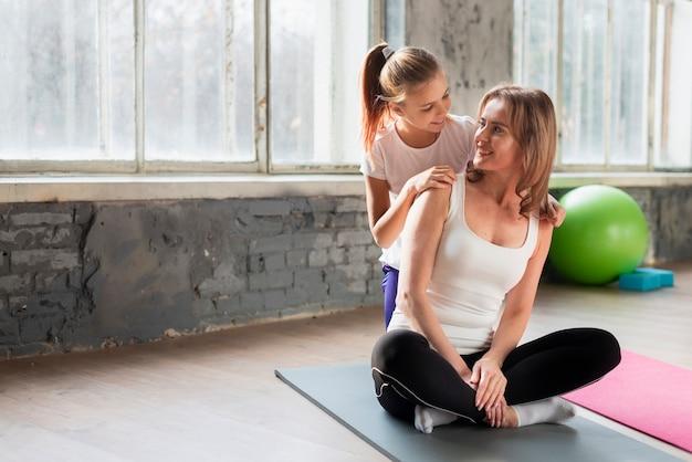 Figlia che abbraccia mamma che fa posa di yoga