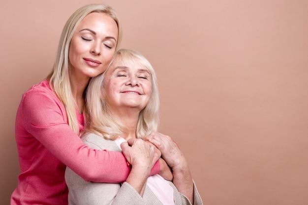 Figlia che abbraccia sua madre con gli occhi chiusi e lo spazio della copia