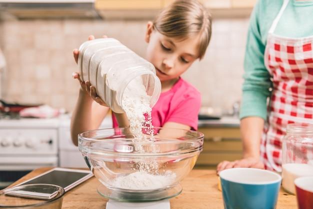 Figlia che aiuta la madre a fare la pasta per pizza