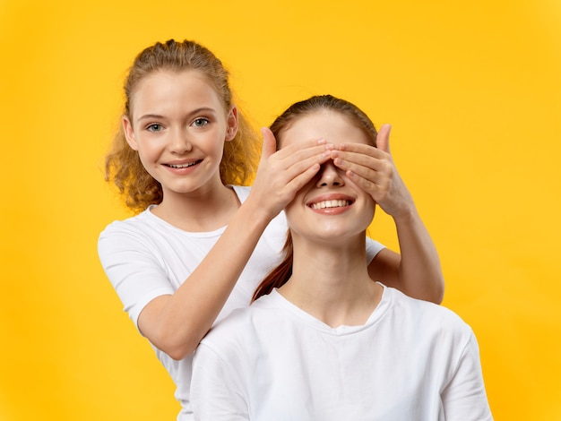 Figlia che copre gli occhi di sua madre per sorprenderla durante la festa della mamma