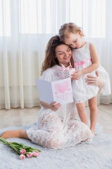 Figlia che dà il contenitore di regalo a sua madre mentre leggono il biglietto di auguri