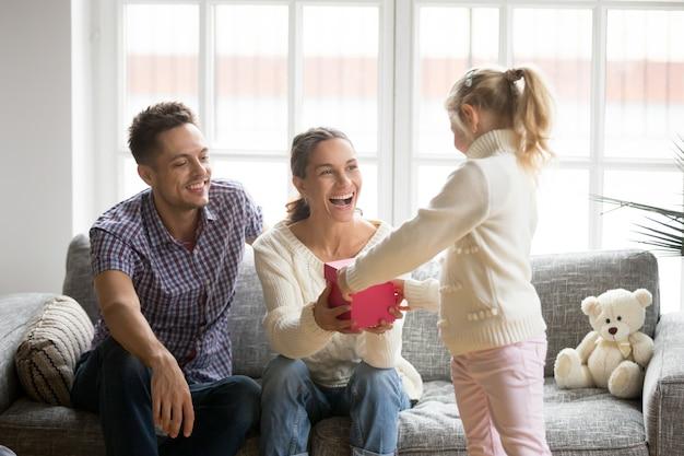 Figlia che dà il contenitore di regalo della mamma che presenta il giorno di madri