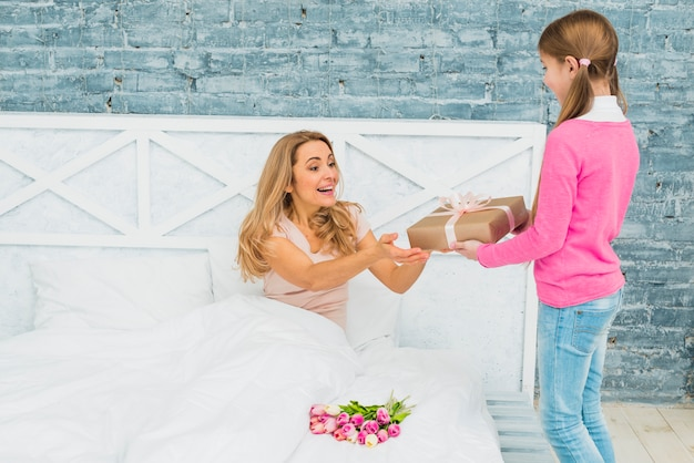 Figlia che dà il regalo alla madre a letto