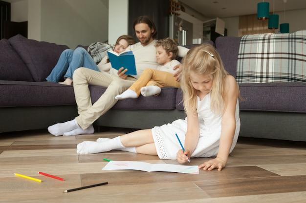 Figlia che gioca sul pavimento mentre i genitori e il figlio leggono il libro