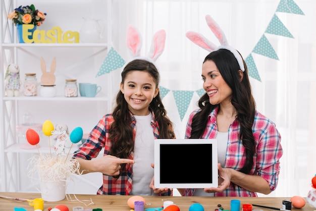 Figlia che indica il dito alla tavoletta digitale tenere da sua madre il giorno di pasqua