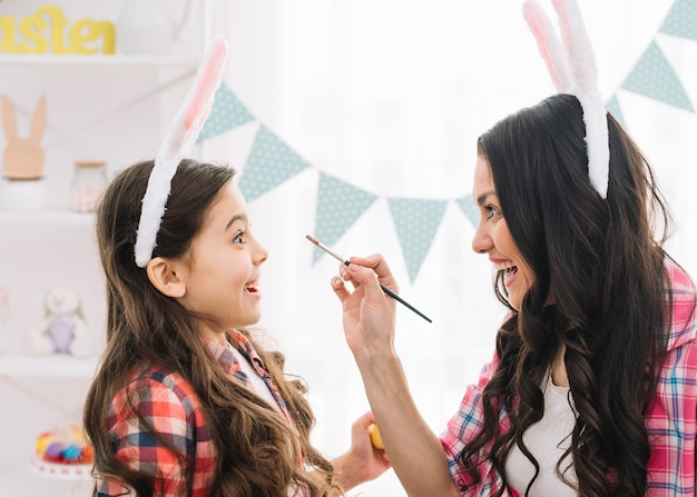 Figlia che sembra sorpresa mentre madre che applica colore sul suo fronte con la spazzola