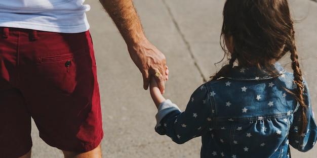 Figlia che tiene la mano di suo padre mentre cammina