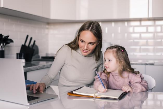 Figlia d'aiuto della giovane madre con i suoi compiti al tavolo nella sala da pranzo
