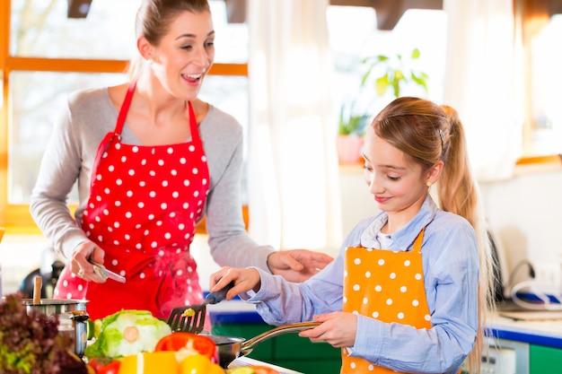 Figlia d'istruzione della madre che cucina a casa