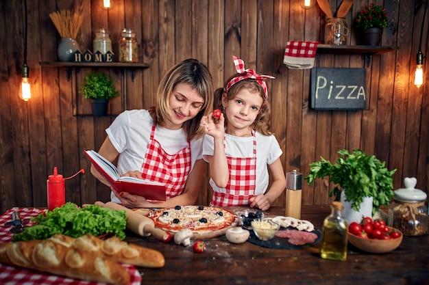 Figlia d'istruzione della madre che cucina pizza e sorridere