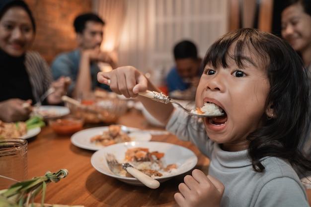 Figlia del bambino che mangia da sola durante la cena