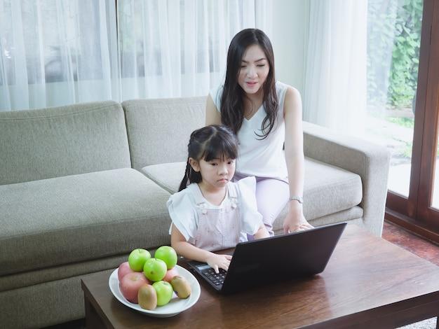 Figlia di sorveglianza della madre che gioca computer