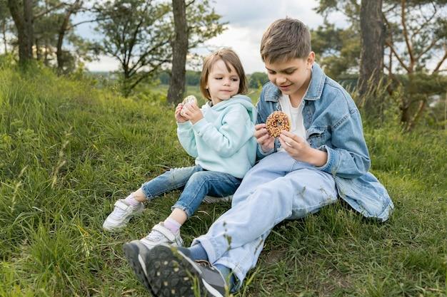 Figlia e figlio che mangiano ciambelle