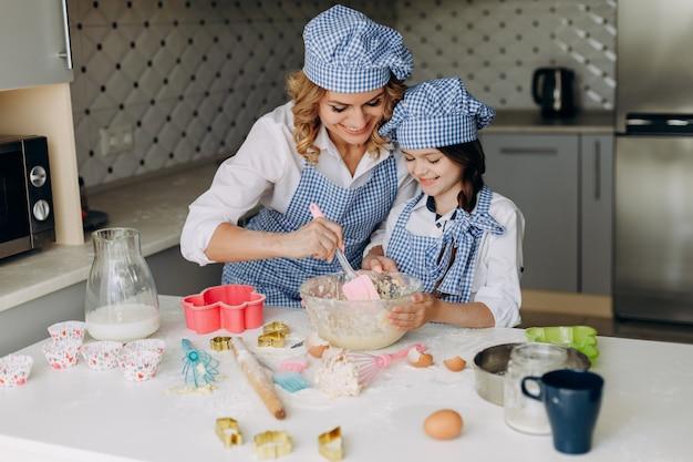 Figlia e madre mescolano l'impasto. concetto di famiglia