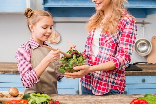 Figlia e madre sorridenti che preparano l'insalata di verdure frondosa nella cucina
