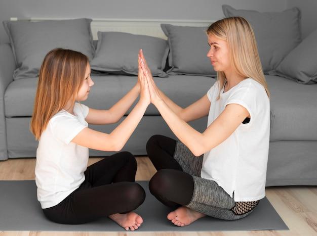 Figlia e mamma praticano sport sul tappetino