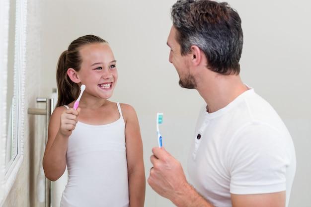 Figlia e padre sorridenti che tengono uno spazzolino da denti nel bagno