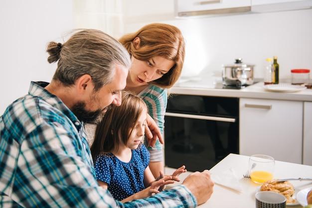Figlia incoraggiante del padre e della madre per digitare messaggio sul ridurre in pani