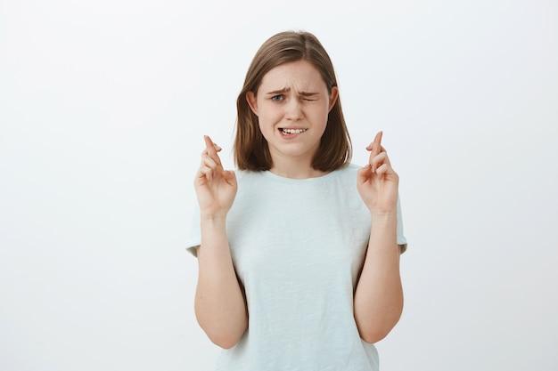 Figlia nervosa insicura incrocia le dita per avere fortuna sbirciare con un occhio la tabella dei risultati mentre aspetta i voti essere ansiosa e preoccupata pregare perché i desideri si avverino