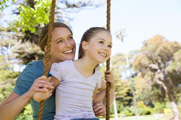 Figlia oscillante della madre felice al parco