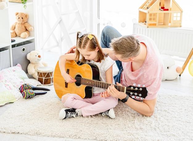 Figlia sorridente con il padre che gioca chitarra