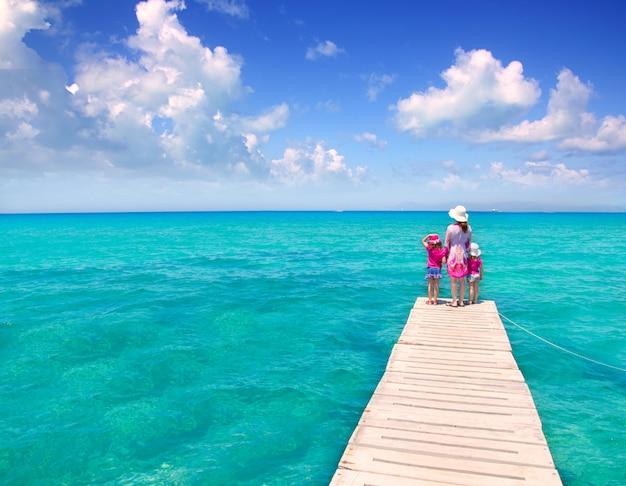 Figlie e madre in pontile sulla spiaggia tropicale