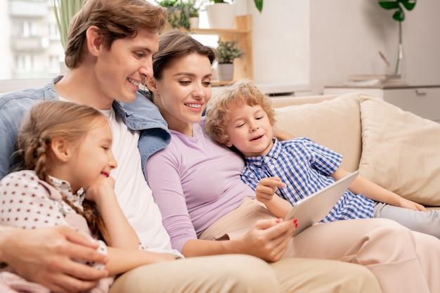 Figlio carino giovane che punta al display del tablet mentre guarda i cartoni animati con i suoi genitori