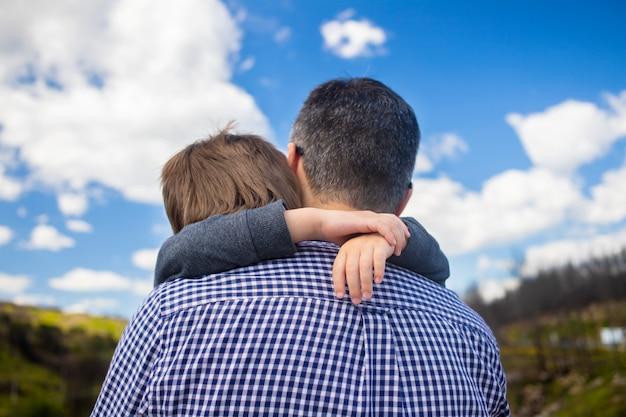 Figlio che abbraccia il padre fuori