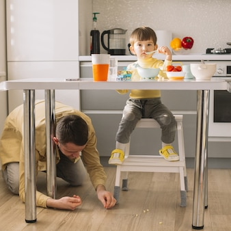 Figlio che mangia e padre che pulisce il pavimento