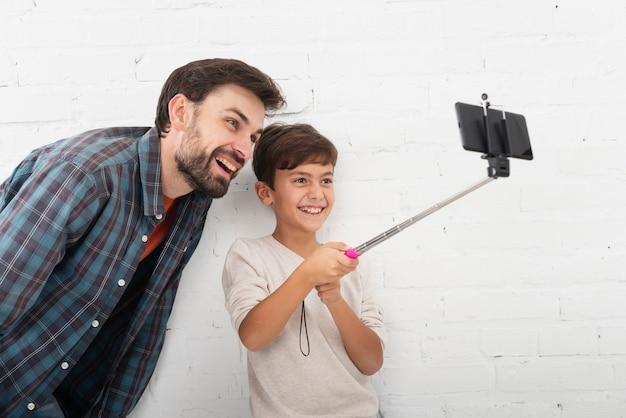 Figlio che prende un selfie con suo padre