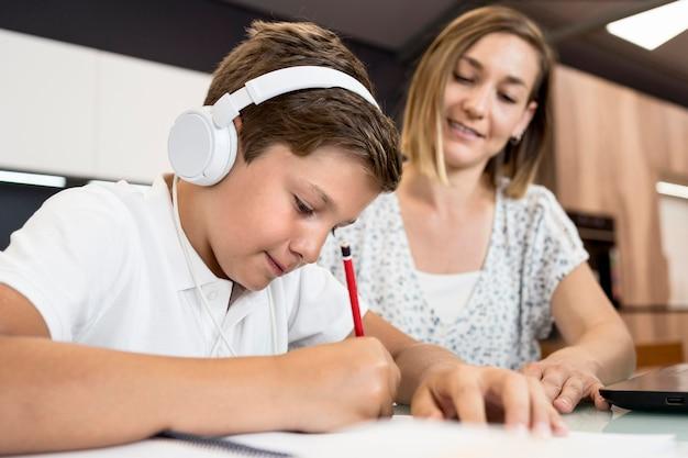 Figlio d'aiuto della madre con i compiti