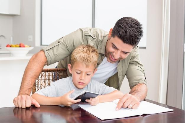 Figlio d'aiuto sorridente del padre con il compito di per la matematica alla tavola