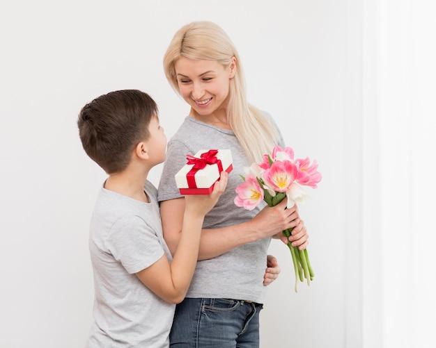 Figlio d'angolo basso che offre regalo alla madre