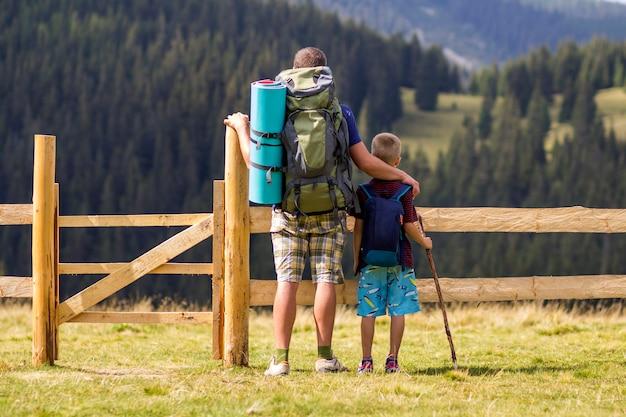 Figlio del figlio e del papà con gli zainhi turistici al recinto di legno basso