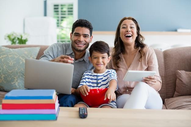 Figlio di guardare la televisione mentre padre e madre utilizzando il computer portatile e la tavoletta digitale a casa
