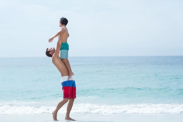 Figlio di trasporto del padre mentre stando alla spiaggia
