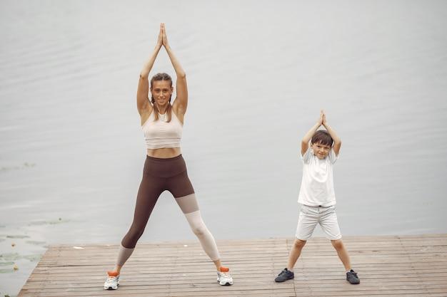 Figlio e madre stanno facendo esercizi nel parco estivo. famiglia sull'acqua.